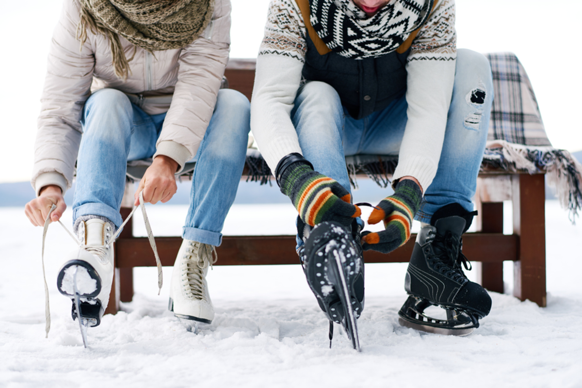 couple-putting-on-ice-skate-outdoors
