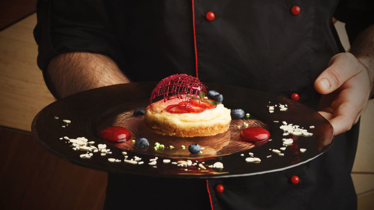 chef-holding-a-dessert-plate-with-elegant-decoration