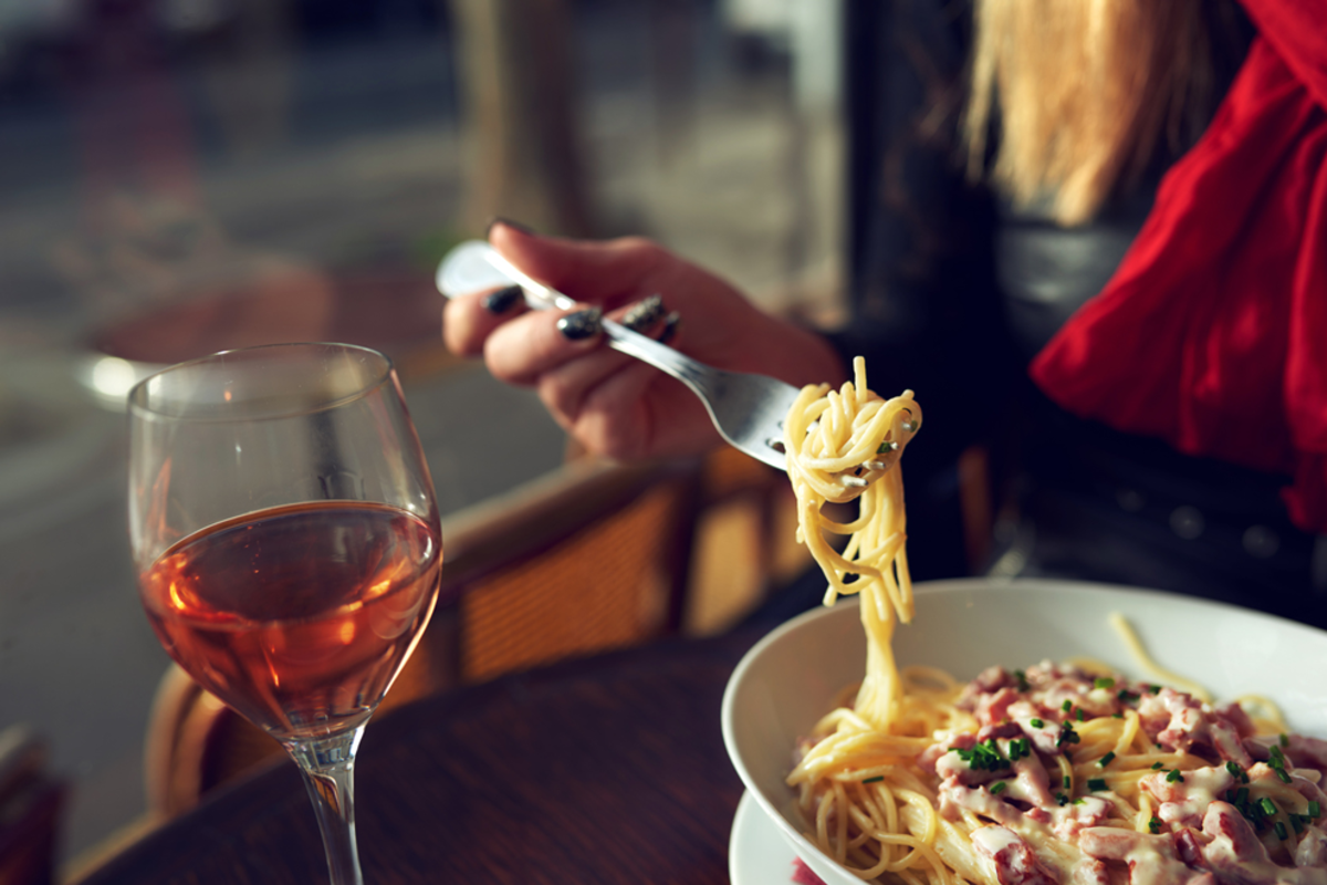 woman-eating-pasta-and-wine-in-nomad-district-italian-market