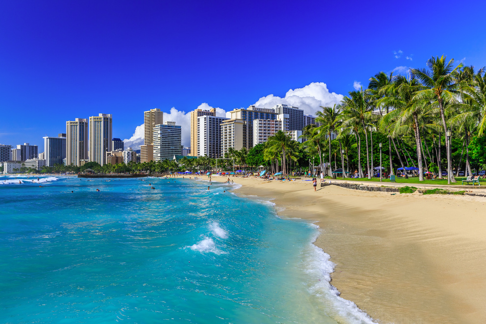 Daytime view of Waikiki Beach with the sand and shoreline if foreground, palm trees on the right and hotels in backdrop