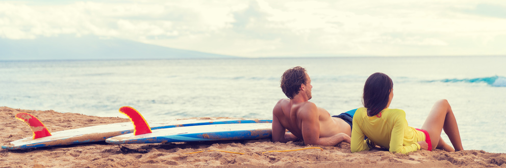 Young man and woman sitting on beach with surfboards, looking out at the ocean