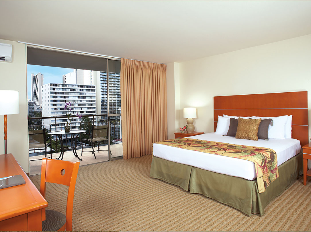 Bedroom with Queen bed, teak wood headboard, desk in foreground and view of Waikiki from balcony