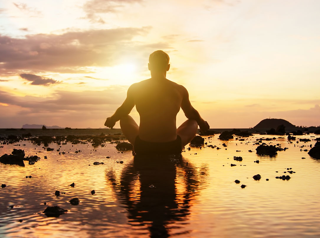 Silhouette of man in sitting yoga pose facing the sunset