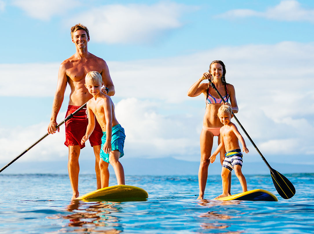 Family of four on standup paddleboards on ocean
