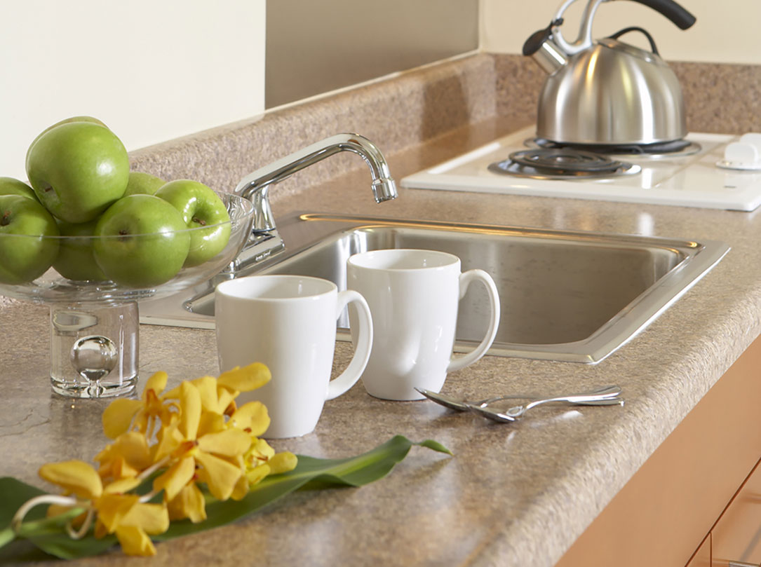 Kitchen counter with sink, stove top, 2 white mugs and bowl of green apples