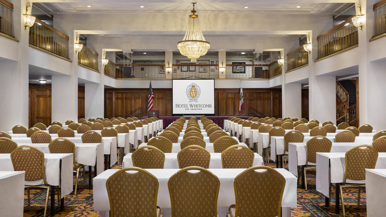 Hotel Whitcomb Ballroom Classroom with projector screen having Hotel Logo and chandelier on the roof