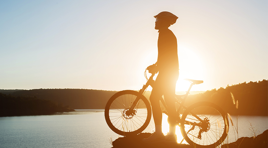 Silhouette of a man wearing a helmet on a bike overlooking a lake and mountains.