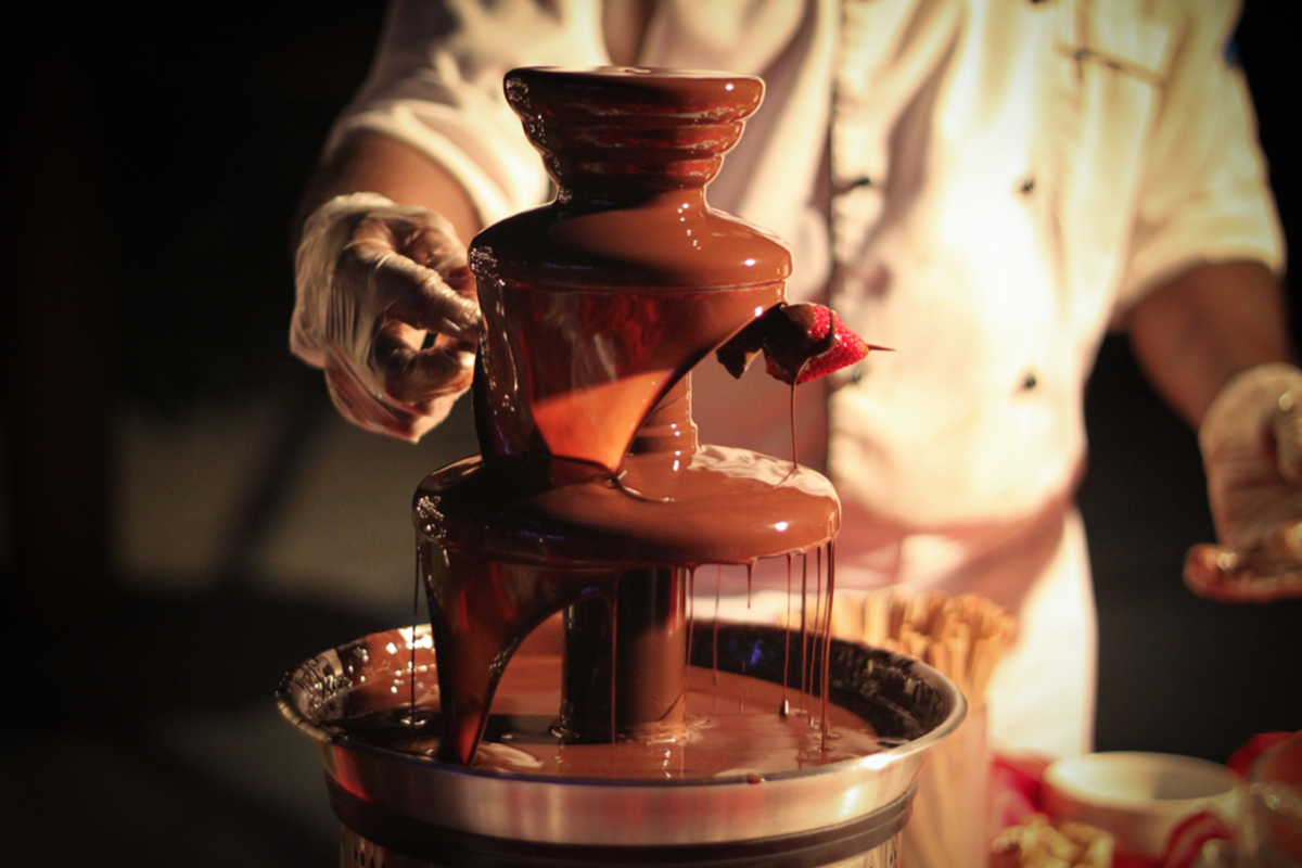 chef-soaking-strawberry-in-chocolate-fountain